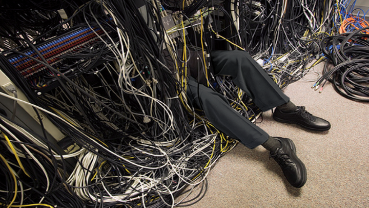 IJT employee working on server with only his legs exposed